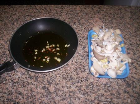 La padella con olio, aglio e prezzemolo ed i funghi tagliati